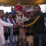 Captain of Azam Sports, Shahid Khan, receiving winner trophy from Mr. Hakim Baloch