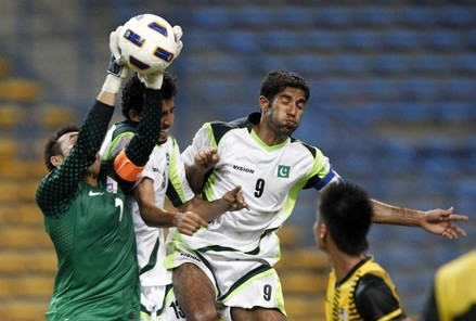 Malaysia's goalkeeper Khairul Fahmi saves ball against Pakistan's Hussain and Asif during their qualifier soccer match for 2012 London Olympic Games, in Shah Alam